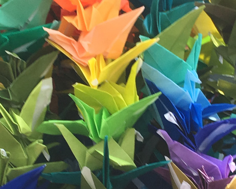 Photo of colourful origami cranes taken behind glass